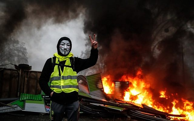 A protester wearing a Guy Fawkes mask makes the 'Victory' sign during a protest of the Yellow Vests against rising oil prices and living costs, on December 1, 2018, in Paris. (AFP/Abdulmonam Eassa)
