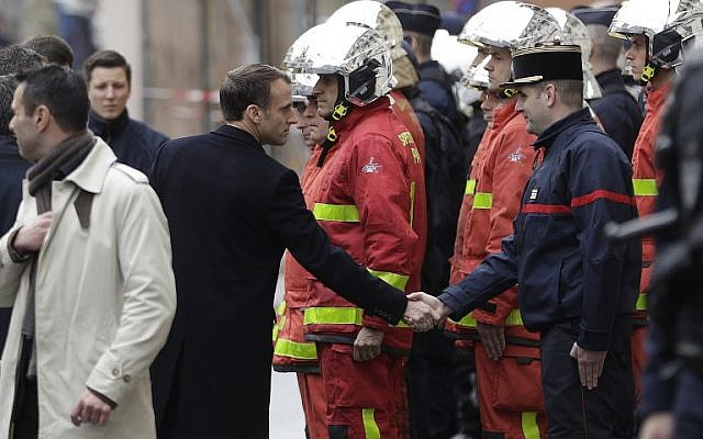 """French President Emmanuel Macron, left, shakes hands with a firefighter during a visit in Paris on December 2, 2018, a day after clashes at a protest of """"yellow vests"""" (gilets jaunes) against rising oil prices and living costs. (Geoffroy Van Der Hasselt/AFP)"""