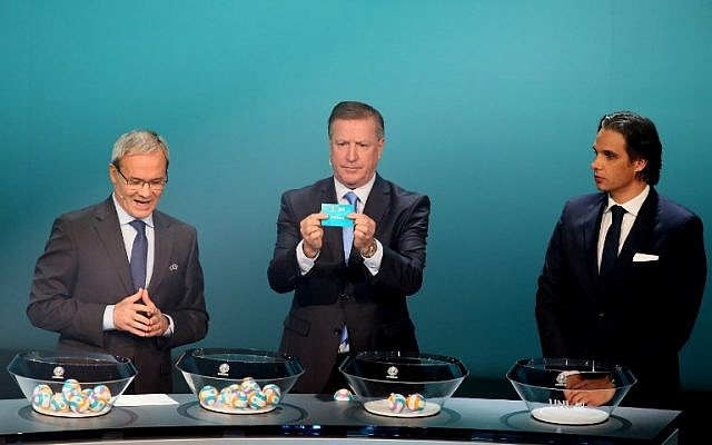 Former Irish footballer Ronnie Whelan (C) holds up a slip of paper after drawing France from the pot flanked by UEFA deputy secretary general Giorgio Marchetti (L) and former Portuguese footballer Nuno Gomes (R) during the UEFA Euro 2020 football competition qualifying draw in Dublin on December 2, 2018. (Photo by Paul FAITH / AFP)
