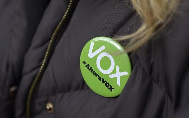 """In this file photo taken on December 01, 2018 a woman wears a pin reading """"Vox, now"""" during a demonstration called by the far-right party VOX against Catalan separatists in Madrid. - A far-right party won seats in a Spanish regional parliament for the first time since the country returned to democracy following the death of longtime dictator Francisco Franco in 1975. (Photo by OSCAR DEL POZO / AFP)"""