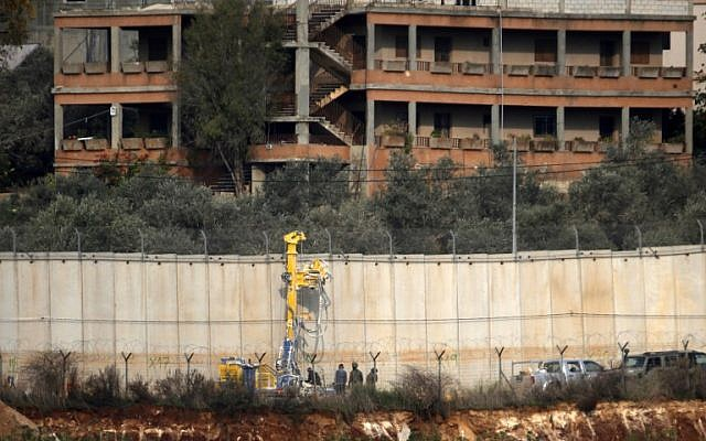 Israeli soldiers standing by excavation machinery near the border wall with Lebanon in the area of Metulla, December 4, 2018.(JALAA MAREY/AFP)