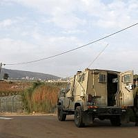 This picture taken on December 4, 2018 near the northern Israeli town of Metula, shows Israeli soldiers standing outside a military vehicle near the border with Lebanon. (JALAA MAREY / AFP)