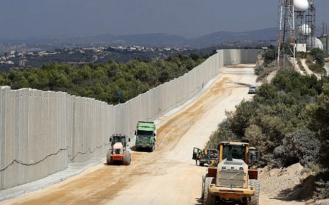 A file photo taken on September 5, 2018 near the Rosh Hanikra border crossing in northern Israel, shows tractors along a new wall on the Israeli-Lebanese border. (JACK GUEZ / AFP)