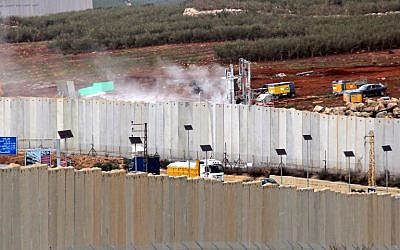 This picture taken on December 4, 2018, from the southern Lebanese village of Kfar Kila shows a view of Israeli machinery operating behind the border wall in Israel (R). (Ali DIA / AFP)