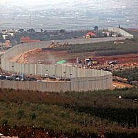 This picture taken on December 4, 2018 from the southern Lebanese village of Kfar Kila shows a view of Israeli machinery operating behind the border wall in Israel. (Ali Dia/AFP)