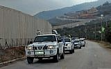 United Nations Interim Forces in Lebanon (UNIFIL) military police cars drive past a concrete separation barrier between the southern Lebanese village of Kfar Kila and Israel on the border between the two countries on December 4, 2018 (Ali DIA / AFP)