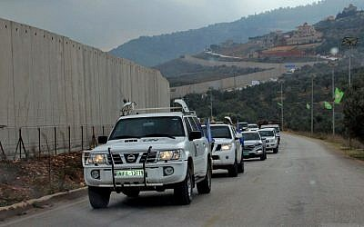 United Nations Interim Forces in Lebanon (UNIFIL) military police cars drive past a concrete separation barrier between the southern Lebanese village of Kfar Kila and Israel on the border between the two countries on December 4, 2018 (Ali Dia/AFP)
