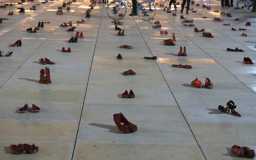 Israelis walk past an installation of red shoes during a rally against domestic violence in Tel Aviv on December 4, 2018. (JACK GUEZ / AFP)