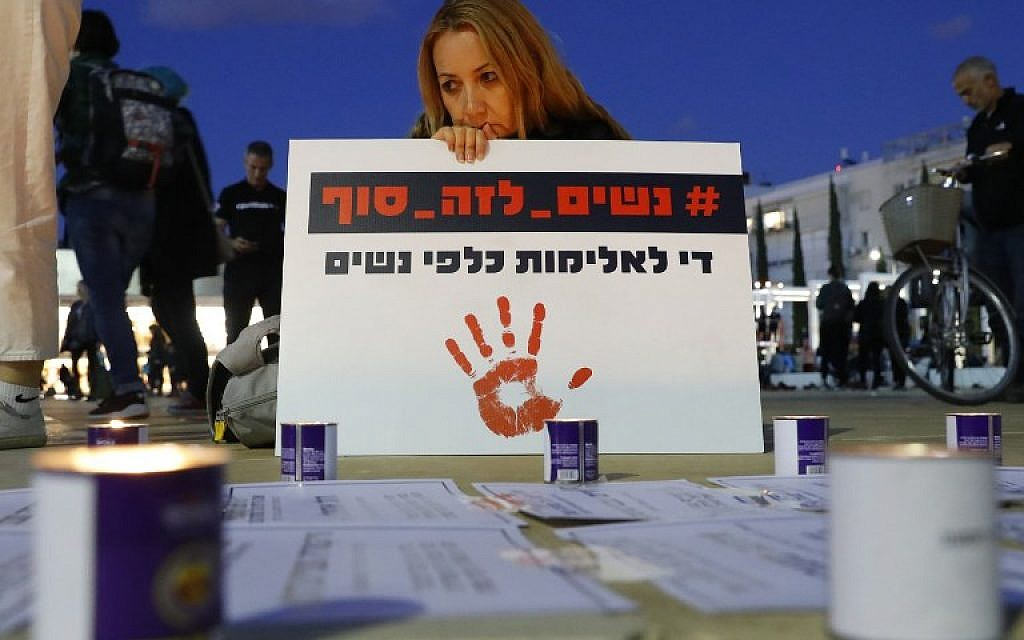 "A woman holds a placard which reads in Hebrew ""Stop the violence against women"" during a rally against domestic violence in Tel Aviv on December 4, 2018. (Photo by JACK GUEZ / AFP)"