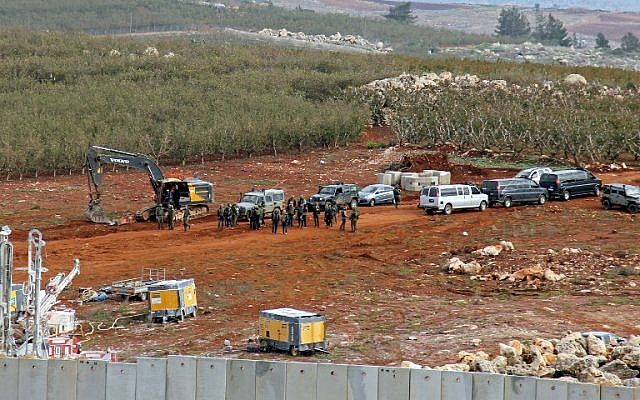 A picture taken on December 5, 2018, from a position near the southern Lebanese village of Kfar Kila shows members of the Israeli military, excavators, trailers, and other vehicles operating on the other side of the border. (Ali Dia/AFP)