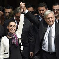 Mexican President Andres Manuel Lopez Obrador (R) raises the hand of Mexico Citys new mayor Claudia Sheinbaum (L), after her swearing-in ceremony at the local Congress in Mexico City on December 05, 2018 (ALFREDO ESTRELLA / AFP)