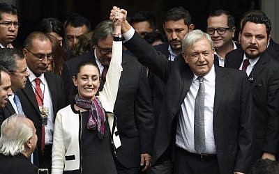 Mexican President Andres Manuel Lopez Obrador (R) raises the hand of Mexico City's new mayor Claudia Sheinbaum (L), after her swearing-in ceremony at the local Congress in Mexico City on December 05, 2018 (ALFREDO ESTRELLA / AFP)