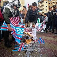 Palestinians burn flags during a demonstration against an upcoming UN General Assembly vote on a US-drafted resolution condemning the Palestinian Hamas movement in the town of Rafah in the southern Gaza Strip on December 6, 2018. ( SAID KHATIB / AFP)