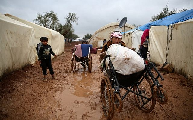 Syrian children walk in the mud after heavy rain at a displacement camp outside Shamarin, near the border with Turkey in the northern Aleppo province, on December 6, 2018. (Nazeer AL-KHATIB / AFP)