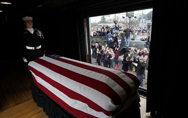 The flag-draped casket of former US President George H. W. Bush passes through Magnolia, Texas, on December 6, 2018, along the route from Spring to College Station, Texas. (AFP/David J. Phillip/Pool)