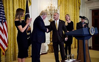 Andrew Pollack, father of Stoneman Douglas High School mass shooting victim Meadow Pollack, shakes hands with US President Donald Trump during a Hanukkah reception in the  White House  in Washington, DC, December 6, 2018. (AFP/Brendan Smialowski)