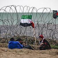 Palestinian youths sit next to a Palestinian flag by the barbed-wire fence along the border with Israel east of Gaza City during a border demonstration on December 7, 2018. (Said Khatib/AFP)