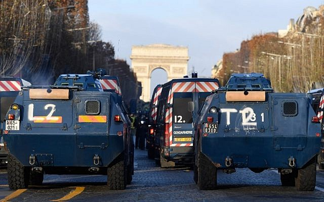 "A picture taken on December 8, 2018 in Paris at the Arc de Triomphe shows Gendarmerie armored vehicles and vans parked during a ""yellow vests"" (gilets jaunes) protest ( Bertrand GUAY / AFP)"