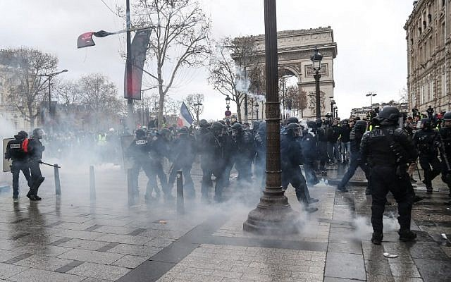 'Yellow vest' protesters clash with riot police amid tear gas on the Champs Elysees in Paris, France, on December 8, 2018. (AFP/Zakaria Abdelkafi)
