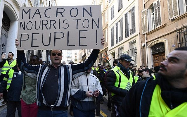 """A man holds a sign reading """"Macron feed your People"""" as protesters wearing """"yellow vests"""" (gilets jaunes) demonstrate on December 8, 2018 in Marseille, southern France, during a protest against rising costs of living they blame on high taxes. (Boris Horvat/AFP)"""