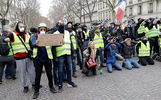 """A protester holds a sign reading """"Macron stop hiding"""" near the Champs Elysees avenue in Paris on December 8, 2018 during a """"yellow vests"""" (gilets jaunes) demonstration protesting rising costs of living they blame on high taxes. (Thomas Samson/AFP)"""