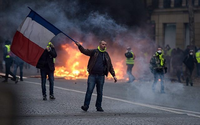 """A """"yellow vest"""" protestor waves a French flag during clashes with riot police amid tear gas near the Champs Elysees in Paris on December 8, 2018. (Lucas Barioulet/AFP)"""