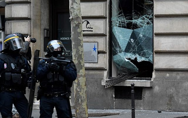 """Riot police stand in front of a broken window during """"yellow vest"""" protests near the Champs Elysees avenue in Paris on December 8, 2018. (Bertrand Guay/AFP)"""