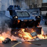 "A gendarmerie armored vehicle drives past fires lit during ""yellow vest"" protests near the Champs Elysees avenue in Paris on December 8, 2018. (Bertrand Guay/AFP)"