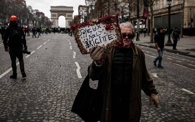 """A protestor holds a sign reading """"Merry Christmas Brigitte (Macron)"""" during a """"yellow vests"""" (gilets jaunes) demonstration against the rising cost of living in front of the Arc de Triomphe in Paris on December 8, 2018. (Abdul Abeissa/AFP)"""
