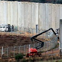 Israeli machinery operates next to a concrete wall separating Israel and Lebanon, in a photograph taken from the southern Lebanese village of Kfar Kila, near the border with Israel, on December 9, 2018. (Ali Dia/AFP)