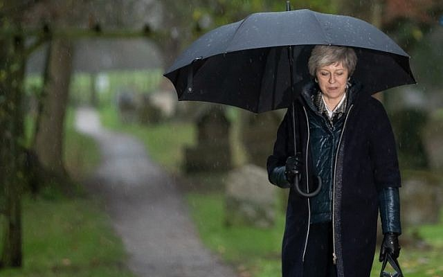 Britain's Prime Minister Theresa May shelters from the rain under an umbrella after attending a church service near her Maidenhead constituency, west of London on December 9, 2018. (Daniel Leal-Olivas/AFP)