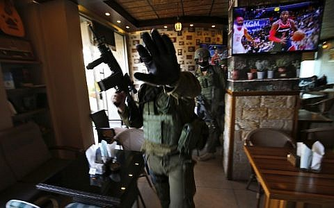 Israeli soldiers stand inside a restaurant during a raid in the West Bank city of Ramallah, on December 10, 2018, following a drive-by shooting attack next to a settlement the previous day in which many Israelis were injured. (ABBAS MOMANI / AFP)