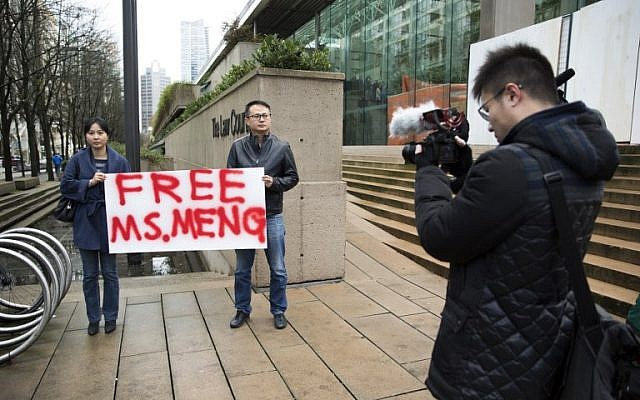 Ada Yu, left, of Vancouver and a man who wished to remain unidentified, hold a sign in favor of the release of Huawei Technologies Chief Financial Officer Meng Wanzhou outside her bail hearing at British Columbia Superior Courts following her December 1 arrest in Canada for extradition to the US in Vancouver, British Columbia on December 10, 2018. (Jason Redmond / AFP)