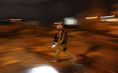An Israeli soldier walks during clashes with Palestinian protesters in the West Bank city of Ramallah on December 11, 2018. (ABBAS MOMANI / AFP)