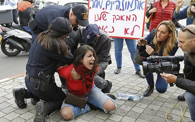 A woman scuffles with police trying to disperse demonstrators from the middle of the street during a rally against domestic violence inTel Aviv on December 12, 2018. (JACK GUEZ / AFP)