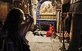 A couple poses for a picture in front of the Grotto of the Nativity, the place where Jesus is said to have been born, inside the Church of the Nativity in the West Bank city of Bethlehem on December 12, 2018. (Thomas Coex/AFP)