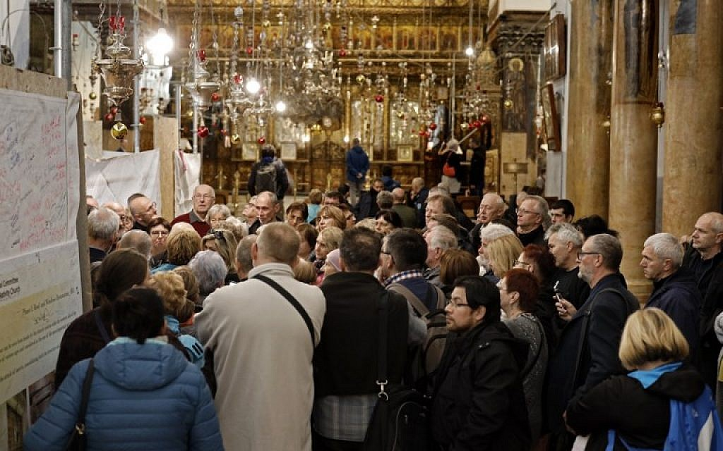 A group of tourists and pilgrims visit the Church of the Nativity, the place where Jesus is said to have been born, in the biblical West Bank town of Bethlehem, on December 12, 2018. (THOMAS COEX / AFP)