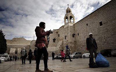 Tourists and Christian pilgrims take pictures outside of the Church of the Nativity, revered as the site of Jesus's birth, in the West Bank city of Bethlehem, on December 12, 2018. (Thomas Coex/AFP)