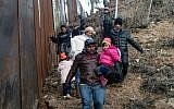 A group of migrants traveling in the Central American caravan, walk alongside the Mexico-US border fence before trying to cross to San Diego County, in Playas de Tijuana, Baja California state, Mexico, on December 12, 2018. (Guillermo Arias/AFP)