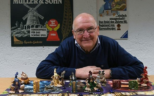 Tom Werneck poses behind a board game at the Bayerisches Spielearchiv archive for board games in Munich, southern Germany, on December 12, 2018 (Christof STACHE / AFP)