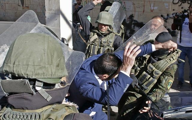 Palestinian security forces beat a Hamas supporter as they try to disperse a rally marking the 31st anniversary of the founding of the terror group in Hebron on December 14, 2018. (Hazem Bader/AFP)