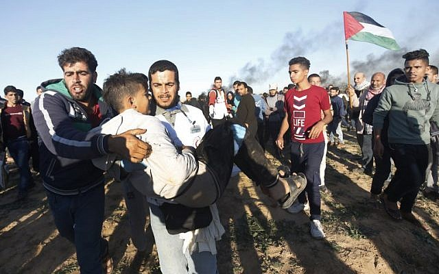 A Palestinian carries a young man away from demonstrations on the border between Israel and Khan Yunis in the southern Gaza Strip, on December 14, 2018. (Said Khatib/AFP)