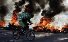 A Palestinian wears a flag with Koranic inscriptions as he rides his bicycle in front of burning tires  near the Hawara checkpoint south of the West Bank city of Nablus on December 14, 2018. (Photo by JAAFAR ASHTIYEH / AFP)