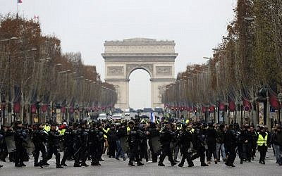 """French riot police take position in front of """"yellow vest"""" protesters on the Champs-Elysees in Paris, on December 15, 2018. (Valery Hache/AFP)"""