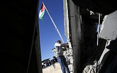 A man raises a Palestinian flag on the ruins of a house belonging to a Palestinian charged with killing an Israeli soldier in the West Bank refugee camp of al-Am'ari, after the Israeli military blew it up on December 15, 2018. (Abbas Momani/AFP)
