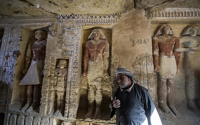 """Said Abdel Aal, an Egyptian archaelogical labourer, stands in a newly-discovered tomb at the Saqqara necropolis, 30 kilometres south of the Egyptian capital Cairo, on December 15, 2018, belonging to the high priest """"Wahtye"""" who served during the fifth dynasty reign of King Neferirkare. (Khaled DESOUKI / AFP)"""
