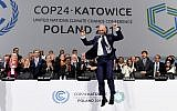 COP24 president Michal Kurtyka jumps at the end of the final session of the COP24 summit on climate change in Katowice, southern Poland, on December 15, 2018. (Janek SKARZYNSKI / AFP)
