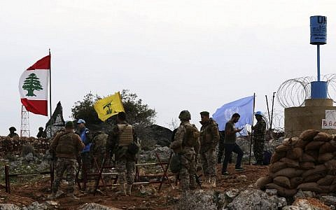 A picture taken from the southern Lebanese village of Meiss al-Jabal on December 16, 2018, shows Israeli soldiers watching as United Nations Interim Forces in Lebanon (UNIFIL) soldiers speak with Lebanese soldiers in front of a Hezbollah flag. (Mahmoud ZAYYAT / AFP)