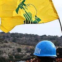 A picture taken from the southern Lebanese village of Meiss al-Jabal on December 16, 2018, shows a United Nations Interim Forces in Lebanon (UNIFIL) soldier monitoring the border between Lebanon and Israel. On his right is a flag of the Lebanese Shiite terror group Hezbollah. (Mahmoud Zayyat/AFP)