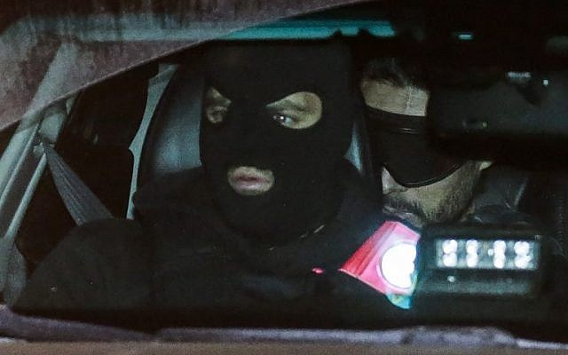 French national Mehdi Nemmouche, right, sits in the back of a police vehicle as he arrives at the courthouse in Brussels on December 20, 2018, for a preliminary hearing in his trial for killing four people in a terror attack at the city's Jewish Museum . (Thierry Roge/Belga/AFP)